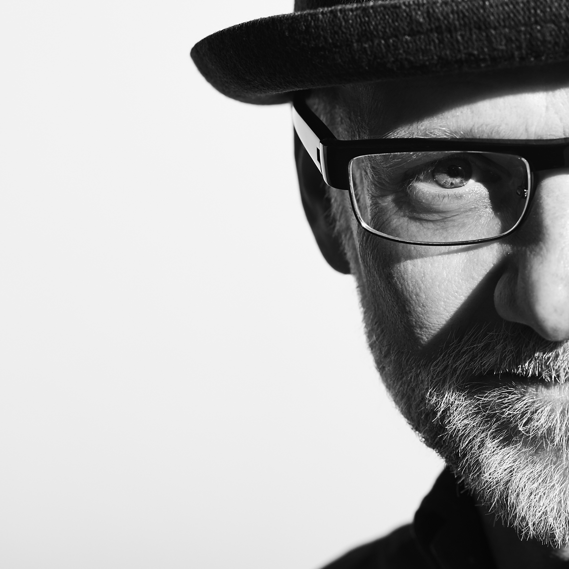 Black and white portrait of white man in a hat with beard and glasses