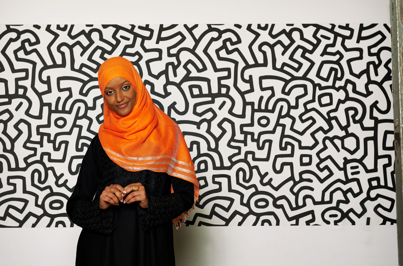 Beautiful Muslim woman in a orange hijab with Warhol backdrop
