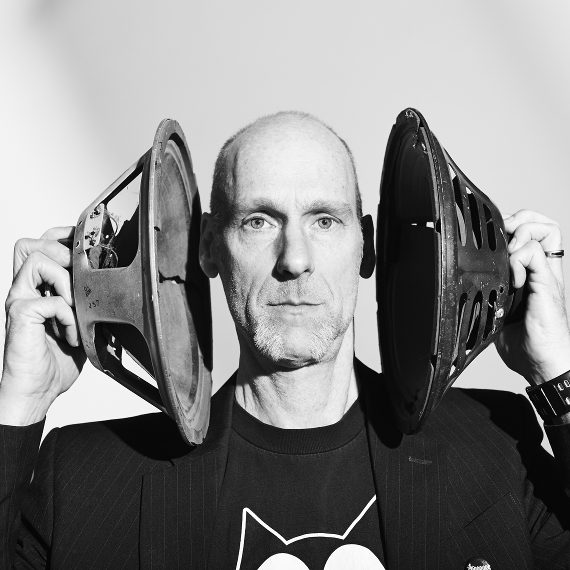 Black and White portrait of bald white man holding speakers over his ears