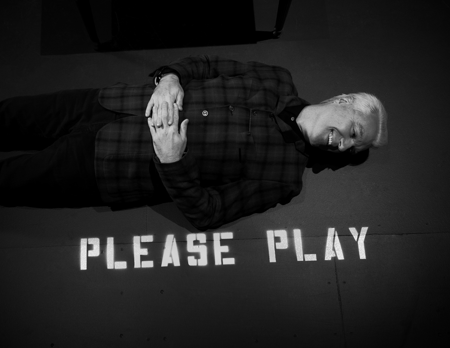 David Byrne laying on the floor with the words Please Play