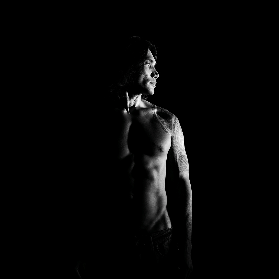 Dramatic Black and white of a topless man with tattoos