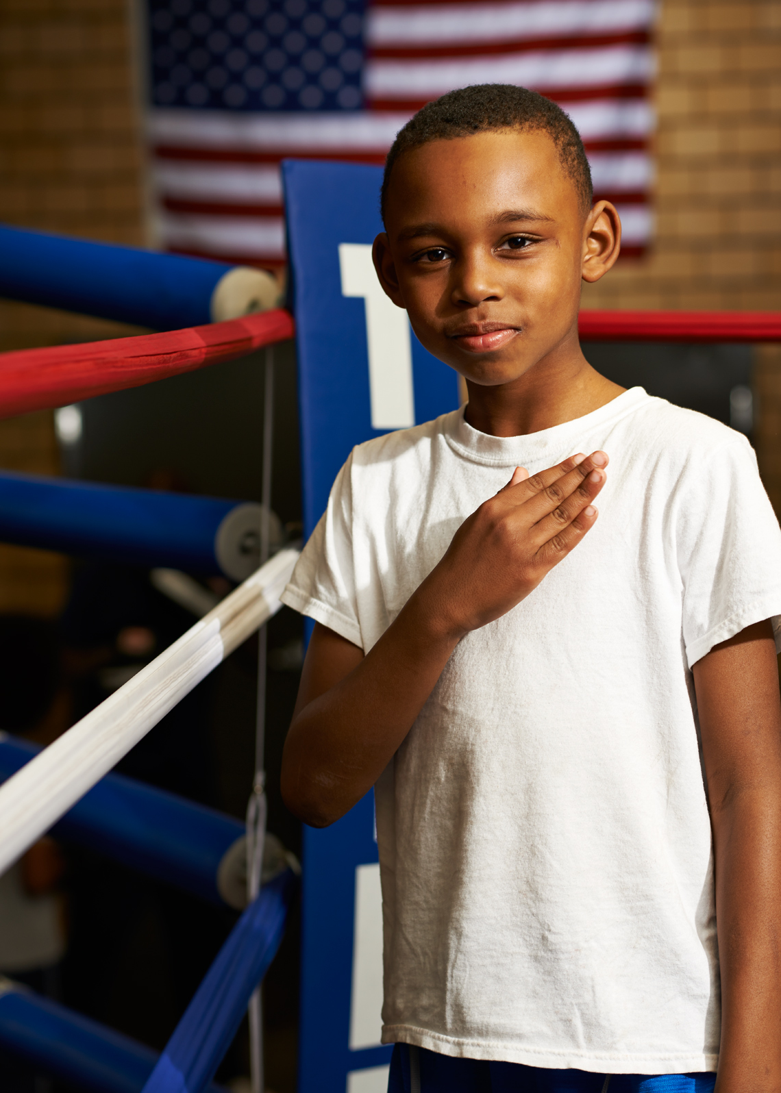 African American Boy with hand over heart and Flag Background