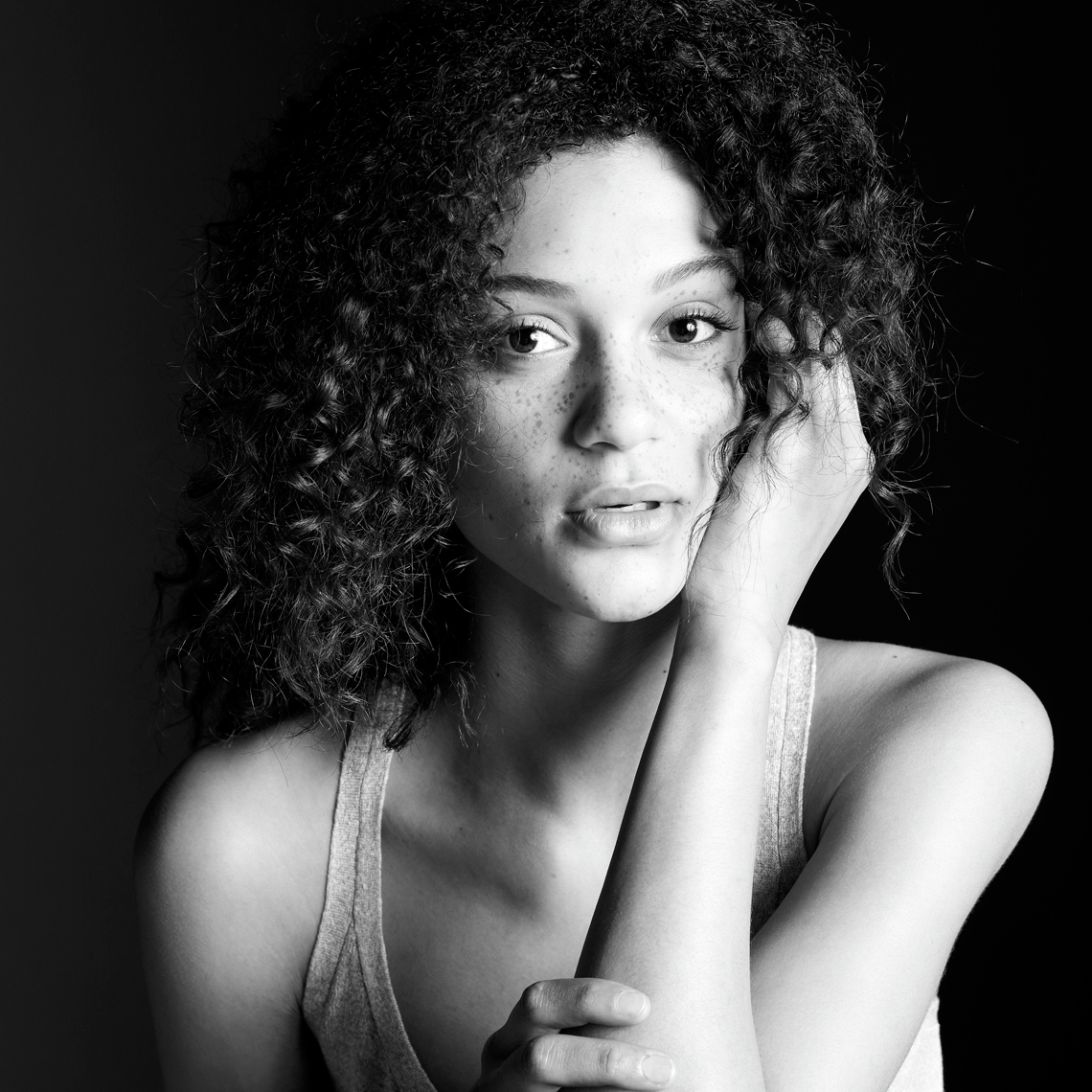 Connected black and white portrait of a mixed race woman with curly hair