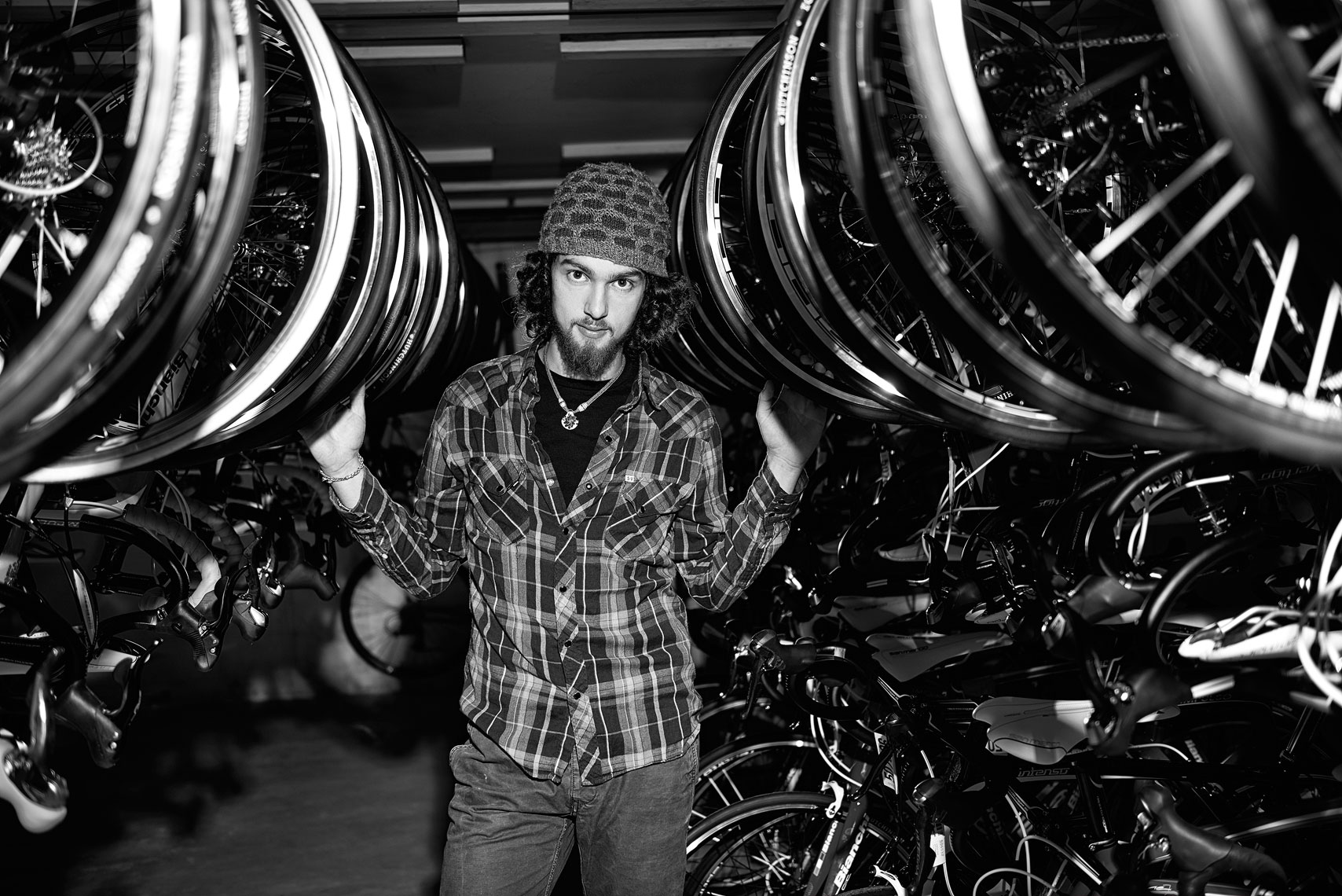 Black and white of a young man in a bike shop millennial beard