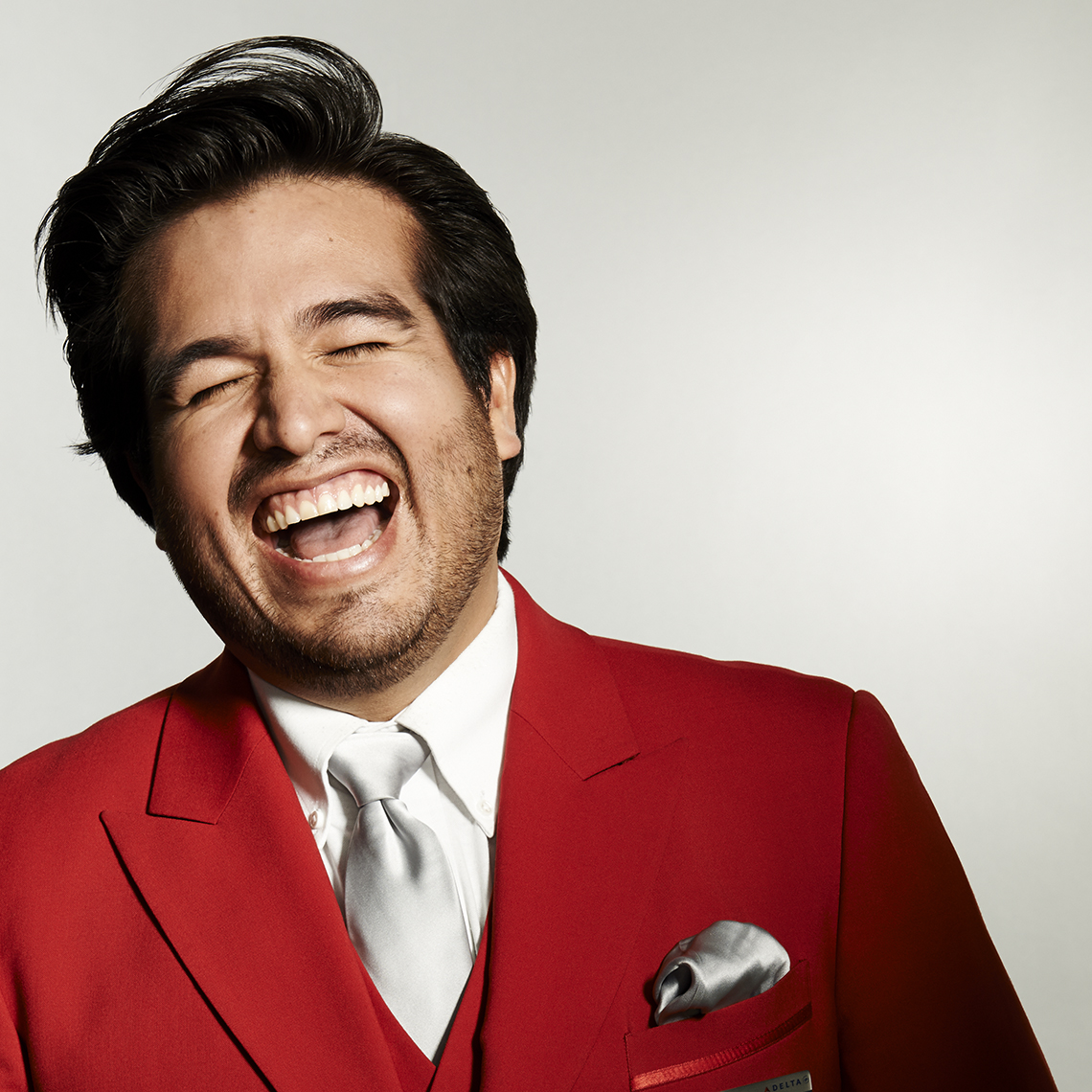 Delta Red Coat_Hispanic Man_Laughing