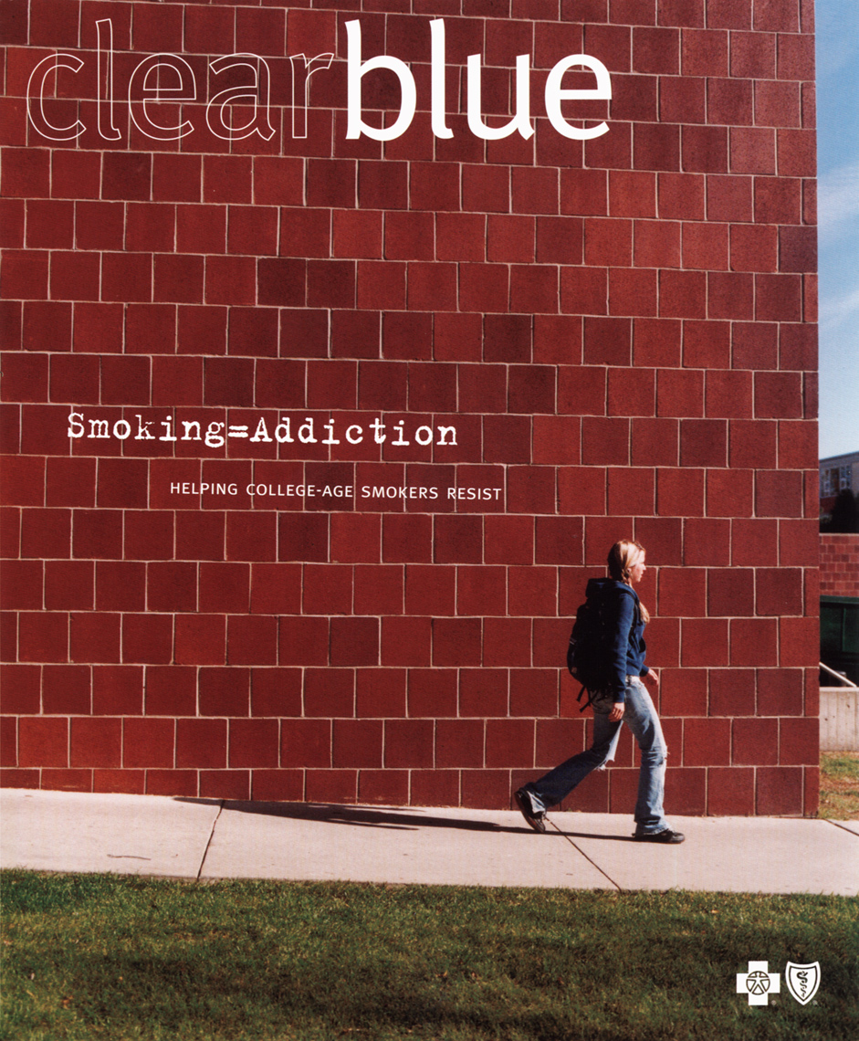 Female student walking on campus Brick Wall Blue Cross