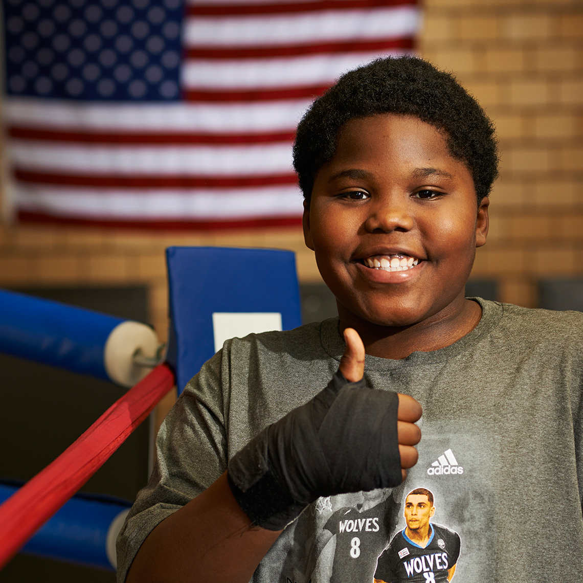 Heavyset kid with thumbs up in boxing ring
